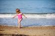 The little girl runs on the beach at the seashore