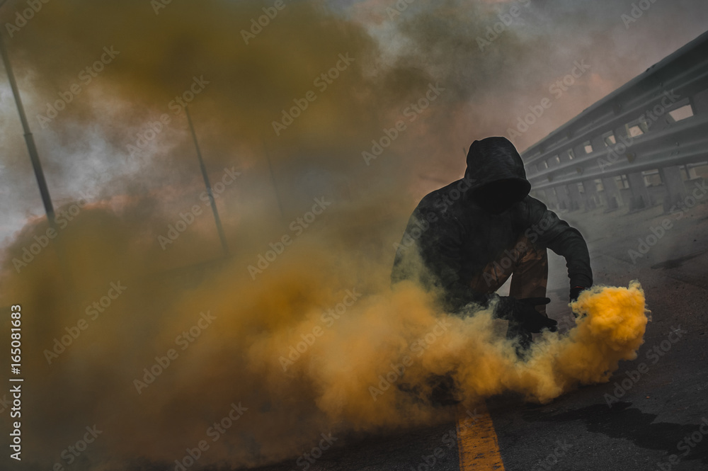 Fényképezés  A brutal guy in a sweatshirt with colored smoke posing on the bridge magnificent