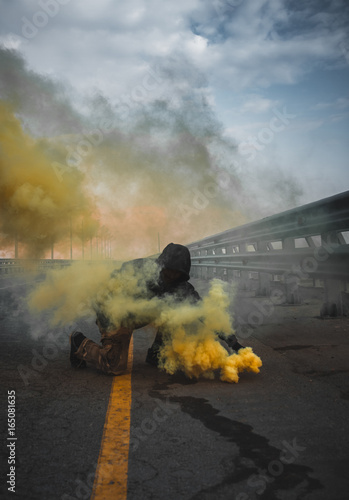 Vászonkép  A brutal guy in a sweatshirt with colored smoke posing on the bridge magnificent