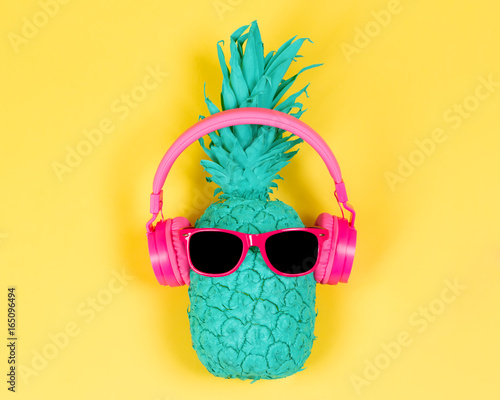 Photo  Pineapple in pink headphones and glasses on a yellow background