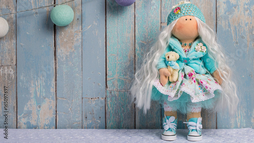 Photographie  tilde doll on a blue background of the boards with.