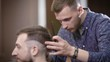 Hipster man getting haircut by hairdresser while sitting in chair. Barber using scissors and comb