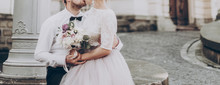 Stylish Wedding Couple With Bouquet. Modern Bride And Groom Holding Fashionable Bouquet  And Hugging At Old Castle. Fine Art Wedding Photo, Romantic Moment, Long Edge