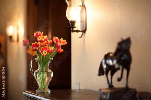 Orange Tulips Bouquet In A Glass Vase Next To A Dark Wooden Horse