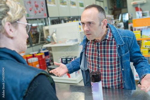 Aggressive customer at shop counter Canvas-taulu