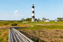 Wooden Ramp Over Marshland, With A Boardwalk Trail To The Bodie Island Lighthouse And Surrounding Buildings, On The Outer Banks Of North Carolina Near Nags Head.
