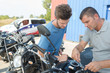Man making adjustment to motorcycle with spanner
