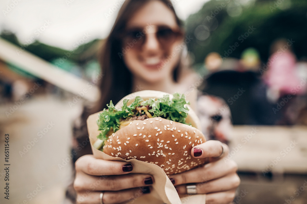 Fototapety, obrazy: big juicy burger in hand. stylish hipster woman holding yummy cheeseburger. boho girl at street food festival. summertime. summer vacation picnic. space for text