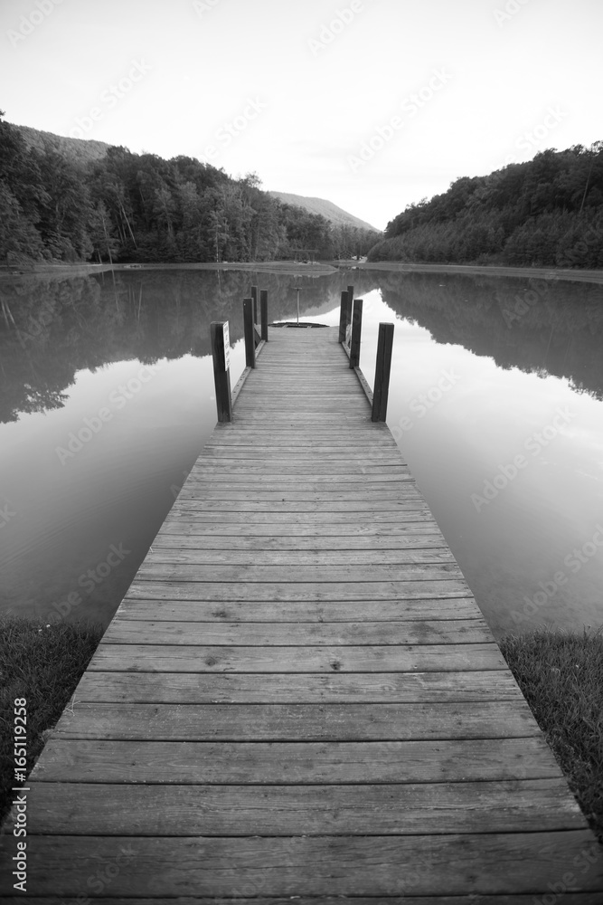Fototapeta Dock on a Lake with Reflective Surface and Dramatic Perspective