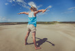 A little girl stands with her arms stretched out to examine her shadow in the sand.