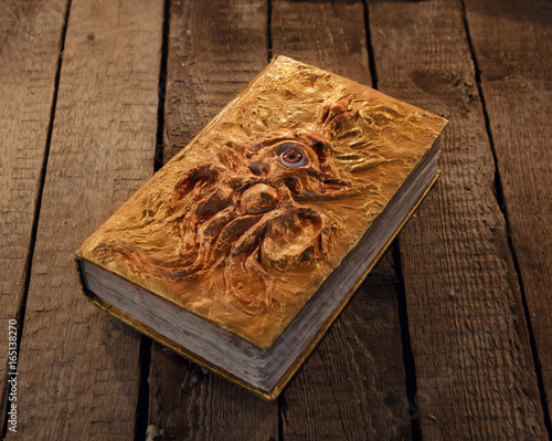 Close up of magic book with golden cover and marine monster image Canvas Print