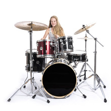 Young Blond Teenage Girl Plays The Drums In Studio Against White Background
