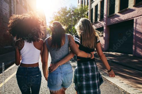 fototapeta na lodówkę Three young women walking together on city street