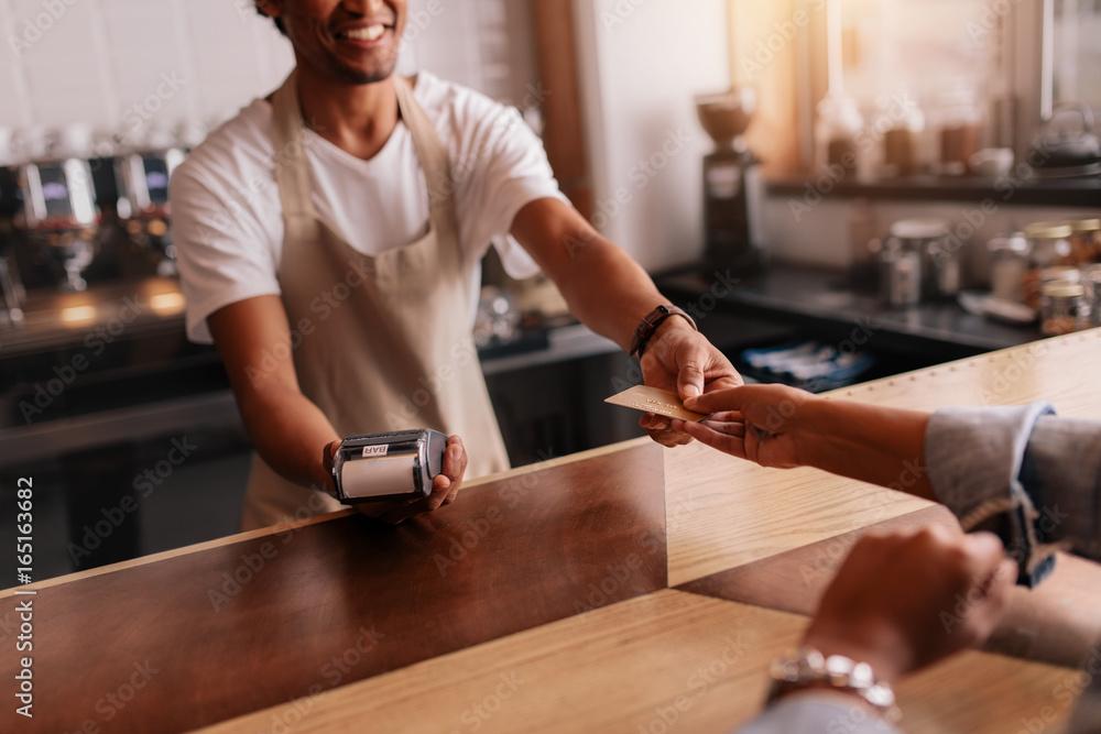 Fototapeta Customer paying through credit card at coffee shop