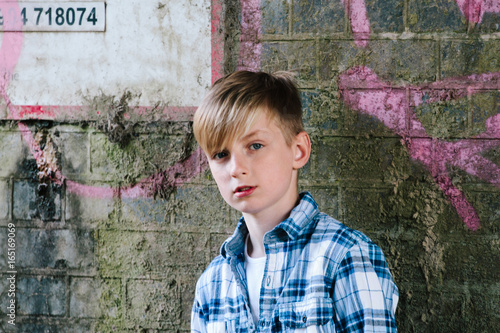 Trendy pre-teen boy standing against a wall.