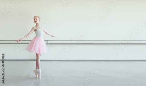 Foto Cute little ballerina in pink ballet costume and pointe shoes is dancing in the room