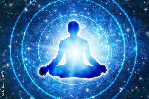 Foto  silhouette of a man sitting in a yoga pose of lotus over blue Universe like a co