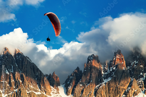 Spoed Foto op Canvas Luchtsport Paraglider flying near high mountains. Dolomites, Italy