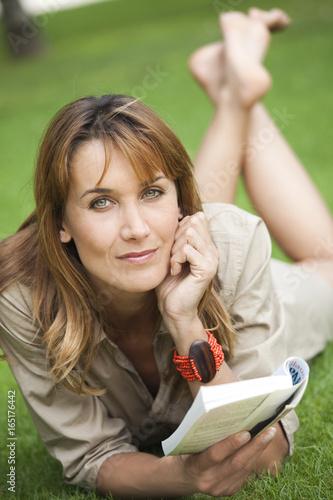 Foto op Plexiglas Aap femme qui lit un livre couchée dans l'herbe