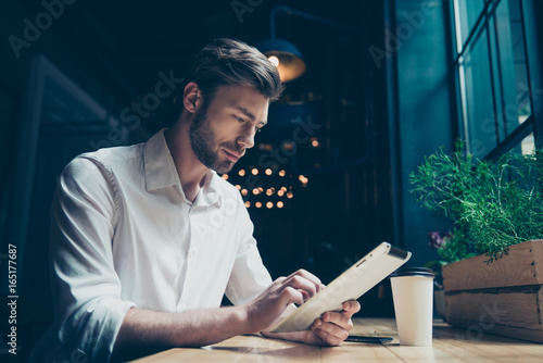 Fotografia  Side view of a young sexy entrepreneur, browsing on his tablet in a dark designe