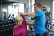 Male personal trainer helping senior woman rehab