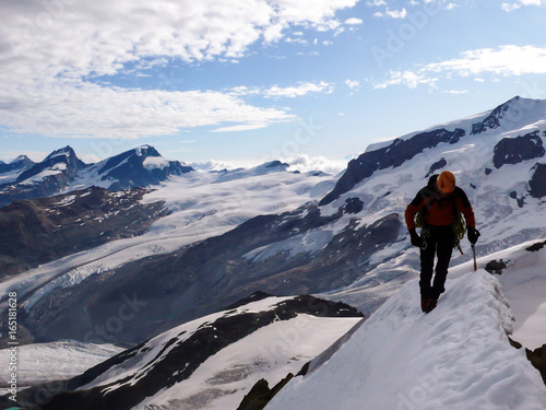 Foto op Plexiglas Alpinisme single male climber free solo on an exposed snowy ridge on a north face route in the Swiss Alps near Zermatt