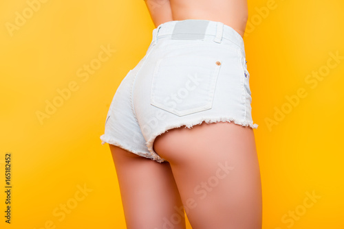 Foto op Canvas Ezel Back view of sexy girl showing her butt in tight white jeans shorts on bright yellow background. So fit and hot!