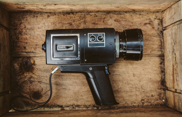 Vintage cinema camera inside an old wooden box