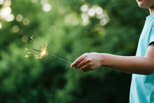 Child Holding A Sparkler In Th...
