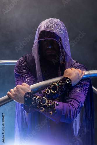 Photo  Fairy-tale character assassin in a purple cloak with a hood with two large cyr w