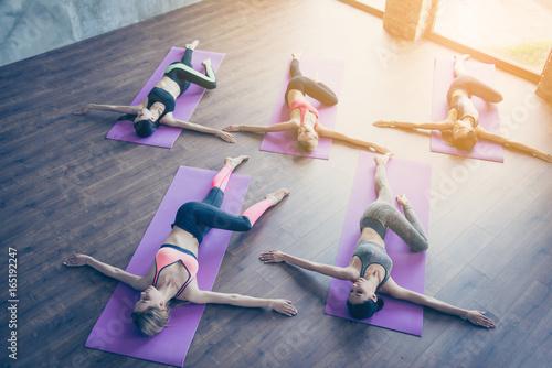 Cuadros en Lienzo Topview of spinal twist, five young sporty women are doing in modern studio, lying on purple mats