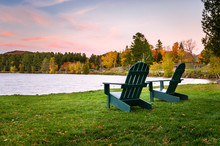 Adirondack Chairs On A Lakeside Lawn At Dusk. Beautiful Autumn Colours.