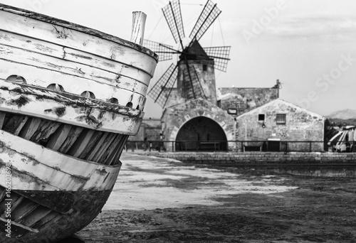 Plakát  Dettagli barca in primo piano con mulino a vento sullo sfondo nella salina di Tr