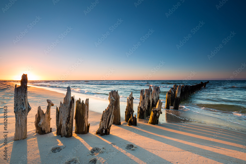 Fototapeta Sunset on the Baltic Sea beach and old wooden breakwater