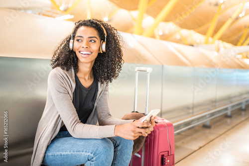 Fotografie, Obraz  happy young black woman listening music with headphones and mobile phone at the