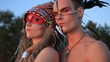 Beautiful native american Indian man and woman in traditional dress at the sea beach at sunset.