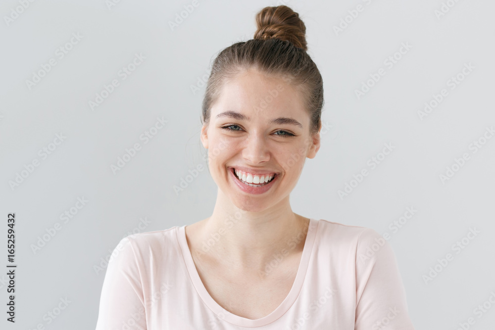 Fototapeta Closeup of positive teenage girl with brown hair tied in bun isolated on gray background with expression of happiness on face, laughing emotionally with excitement as if reacting to funny joke.