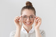 Leinwanddruck Bild - Closeup of attractive young woman isolated on gray background, wearing big round spectacles with thin black frame, touching temples with fingers, smiling with expression of satisfaction and interest.