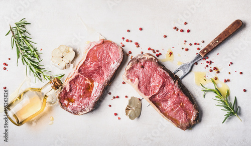 Poster de jardin Viande Raw beef Striploin steaks with oil , spices and meat fork on white stone background, top view, flat lay, horizontal