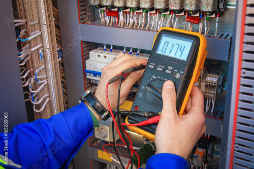 Fotografía Electrical Engineer adjusts electrical equipment with a multimeter in his hand closeup