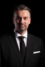 Dramatic Portrait Of Businessman On Black Background In Studio Photo