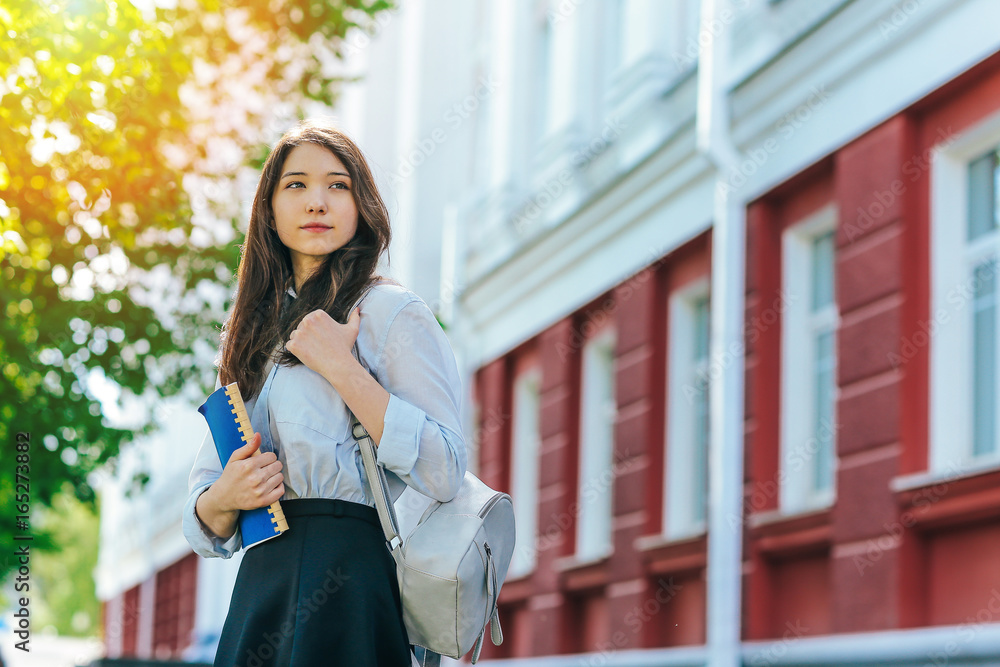 Fototapety, obrazy: Beautiful girl student with a backpack and a textbook standing outdoors with the building of the University on the background
