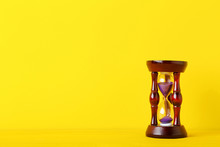 Wooden Hourglass On Yellow Bac...