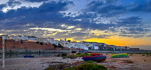 historical part of the Moroccan city on a sunset, settles down on the river bank, several fishing boats in the foreground