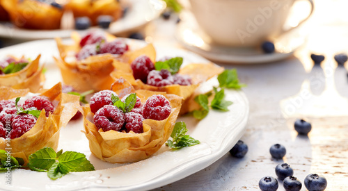 Poster Dessert Phyllo cups with Mascarpone cheese filling topped with fresh Raspberries and mint on a white plate, delicious dessert