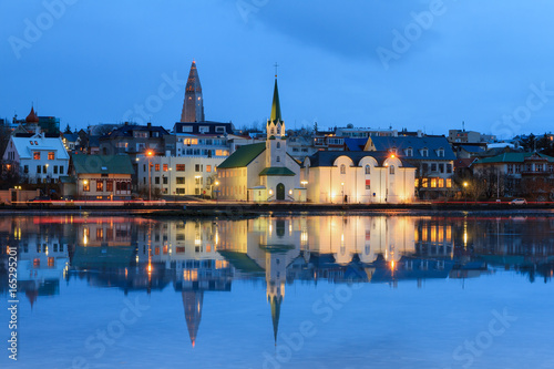 Fotografija  Beautiful reflection of the cityscape of Reykjavik in lake Tjornin at the blue h