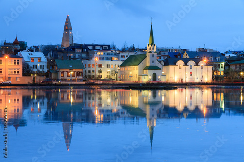 Beautiful reflection of the cityscape of Reykjavik in lake Tjornin at the blue h Fototapet