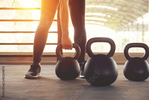 Poster Fitness Fitness training with kettlebell in sport gym with sunlight effect.