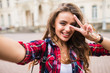 Leinwandbild Motiv Young girl take selfie from hands with phone with victory sign on summer city street urban life concept