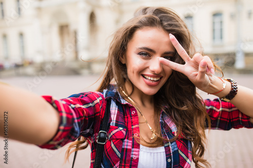 Young girl take selfie from hands with phone with victory sign on summer city street urban life concept